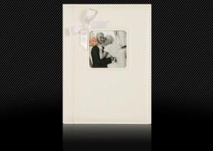 Свадебная фотокнига с белой кожаной обложкой, с оформительными элементами: двойная прострочка, маленькое окошко с фотографией и атласный бантик
