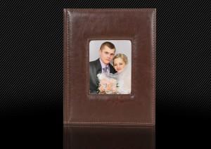 Свадебная фотокнига с темно-коричневой кожаной обложкой оформлена большим окошком