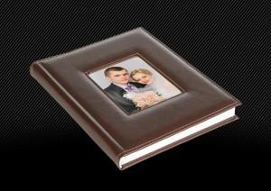 Свадебная фотокнига с темно-коричневой кожаной обложкой оформлена большим окошком, торец